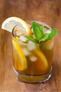 Glass of ice tea with lemon and mint close up on a wooden background Royalty Free Stock Photography