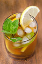 Glass of ice tea with lemon and mint top view on a wooden background Stock Photo