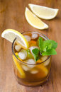 Glass of ice tea with lemon and mint on a wooden background Royalty Free Stock Image