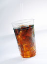 Glass of iced soda carbonated drink served as a takeaway with a straw on a white background Royalty Free Stock Photo