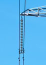 Glass insulators and wires on high towers against blue sky Stock Images