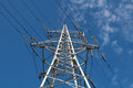 Glass insulators and wires on high towers against blue sky Stock Photo