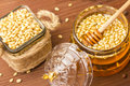 A glass jar of delicious honey with pine nuts. Bank with pine nuts.