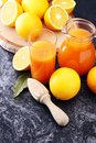 Glass jar of fresh orange juice with fresh fruits on dark table. Royalty Free Stock Photo