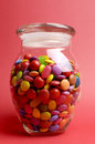 Glass jar full of bright colorful lollies and candy with closed lid against a red background for halloween or christmas treats Royalty Free Stock Photography