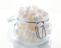 Glass jar full of white sugar cubes on base Royalty Free Stock Images
