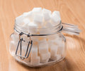 Glass jar full of white sugar cubes on wooden base Stock Photo