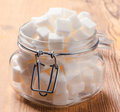 Glass jar full of white sugar cubes on wooden base rustic Royalty Free Stock Photos