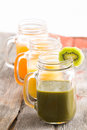 Glass jar of healthy kiwifruit smoothie garnished with a slice fresh kiwi together with jars mango and orange juice in a Royalty Free Stock Photo