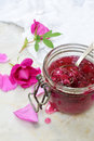 Glass jar and little spoon with tea rose petal jam on light marble background. Copy space for text. Royalty Free Stock Photo