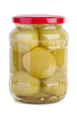 Glass jar with marinated green tomato on the white background Stock Image
