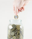 Glass jar with money on a white background. Hand with a coin