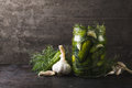 Glass jar of pickles with dill and garlic pickled gherkins on dark metal grey ructic background copy space Royalty Free Stock Photos