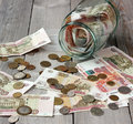 Glass jar and Russian money on the wooden floor. Royalty Free Stock Photo