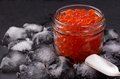 Glass jar with salmon caviar standing in the middle of ice cubes on black slate plate Royalty Free Stock Photo