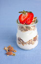 Glass jar with yogurt and granola strawberry on top Royalty Free Stock Image