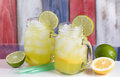 Glass jars filled with cold lemonade on USA national colors for Royalty Free Stock Photo