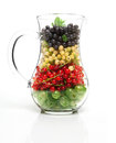 Glass jug with berries ripe on a white background Stock Photos