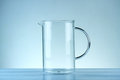 Glass jug on a blue background Stock Photos