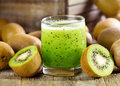 Glass of kiwi juice with fresh fruits on wooden table Stock Photo