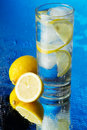Glass of lemon ice water on blue background Royalty Free Stock Photo