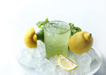 Glass of lemonade with basil leaves, lemons and ice cubes isolated on white Royalty Free Stock Photo
