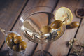 Glass of martini with green olives on a old wooden table Royalty Free Stock Photo