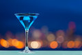 Glass of martini standing against city lights Royalty Free Stock Photo