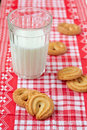 Glass of milk and cookies on a red checkered cloth Royalty Free Stock Photos