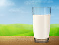 Glass of milk on wooden table on background of blurred landscape