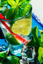 Glass of mojito with lime and mint ice cube close-up red straw on blue background Royalty Free Stock Photo