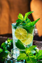 Glass of mojito with lime and mint ice cube close-up red straw on orange background Royalty Free Stock Photo
