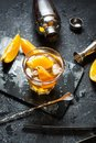 A glass of Negroni cocktail with orange and lemon. Alcoholic drink with rum and vermouth on dark stone table Royalty Free Stock Photo