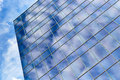 Glass office building and blue sky sunrise sunset capture of clouds reflected in modern window at dusk dawn Stock Photos