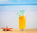 Glass of orange juice on the sea and sandy beach near starfish Royalty Free Stock Photo