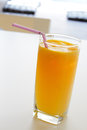 A glass of orange juice with straw in cafe setting Stock Images