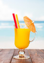 Glass orange juice with straws and umbrella on sea background. Royalty Free Stock Photo