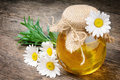 Glass pot of honey with daisies Stock Image