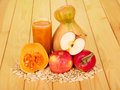 Glass pumpkin juice apples and seeds on background light wood a of a of Stock Photos
