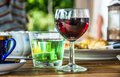 Glass of red vine,coffee and water in table in summer garden Royalty Free Stock Photo