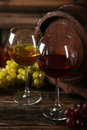 Glass of red and white wine with grapes on brown wooden background Royalty Free Stock Photo