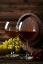 Glass of red and white wine with grapes on the brown wooden background Royalty Free Stock Photo