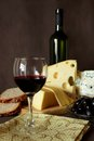 Glass of red wine bottle and several varieties of cheese uncorked poured into a good dry sliced ​​cheese fresh bread olives Stock Photography