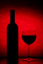 Glass red wine bottle wine black table against red textured background Royalty Free Stock Images