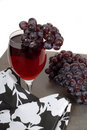 Glass of red wine with grapes and a black and white napkin Royalty Free Stock Image