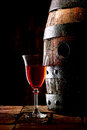 A glass of red wine next to an oak cask old with its stopper out Royalty Free Stock Image