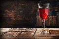 A glass of red wine on an old rustic table