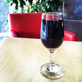 Glass of red wine on the table with chair and plants in background photo taken with iphone Royalty Free Stock Photos