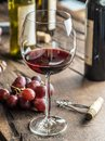 Glass of red wine on the table. Wine bottle and grapes at the ba Royalty Free Stock Photo