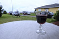 Glass of red wine on a wet table on the veranda Royalty Free Stock Photo